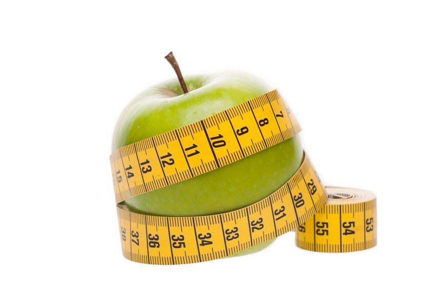 14730887 - dieting concept green apple with measuring tape on white background