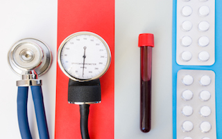 Healthcare, diagnosis and pharmacological treatment of design concept photo. Stethoscope, sphygmomanometer, lab blood sample and pills in blisters are on colored background: white, red, blue, gray