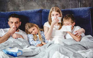 70543509 - family of four has a flue and lying on bed together